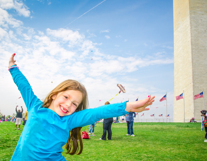 Young girl poses spreads her arms like wings and pretends to fly, inspired by many kites filling the sky at the during a kite festival on the National Mall in Washington, DC. The washington monument stands behind her.